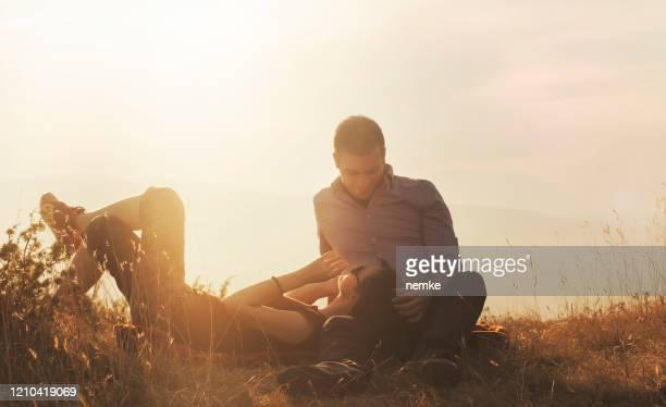 de jonge vrouw die op vriend leunt en hem een kus bij zonsondergang geeft - lying down stockfoto's en -beelden