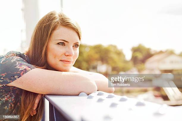 Young woman leaning on bridge.