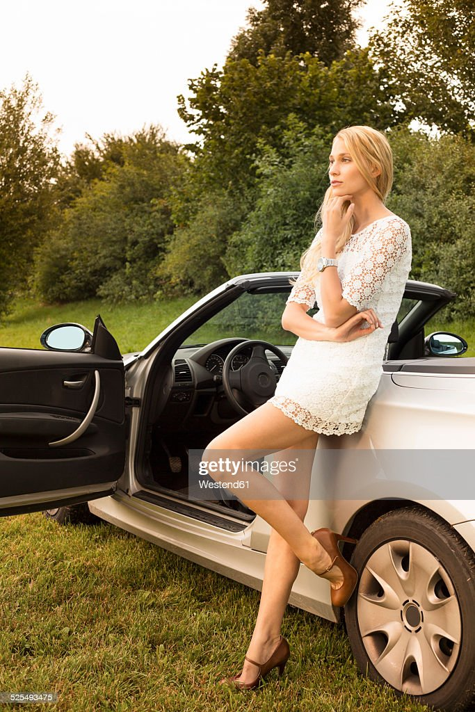Young woman leaning on cabriolet : Stock Photo