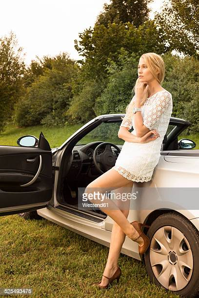 young woman leaning on cabriolet - beautiful legs in high heels stock photos and pictures