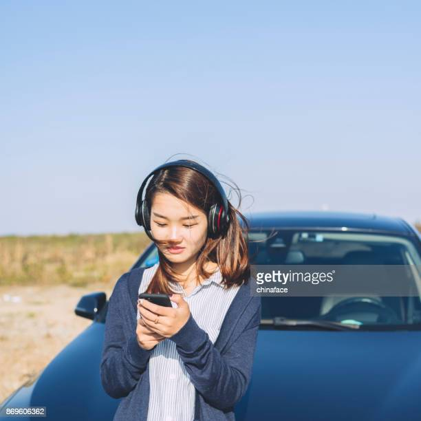 young woman leaning on car hood,using phone with listening to music