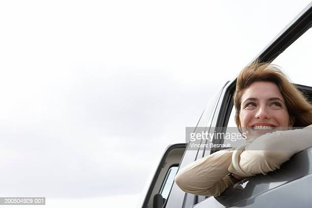 Young woman leaning on car window smiling, close-up, low angle view