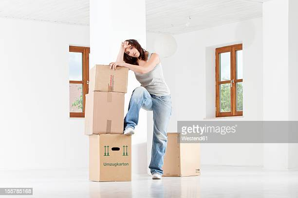 Young woman leaning on cardboard boxes