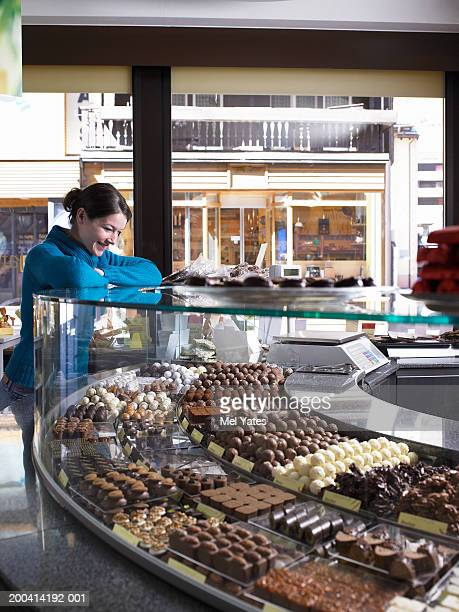 Young woman leaning on counter in chocolate shop, smiling