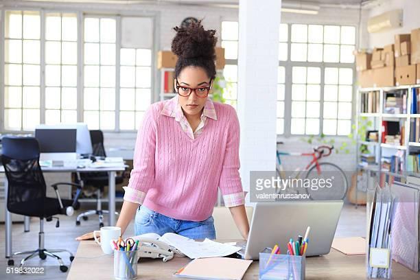 mujer joven apoyarse en el escritorio del área de trabajo - ayudante fotografías e imágenes de stock