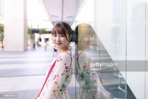 young woman leaning on glass window - akihabara stock pictures, royalty-free photos & images