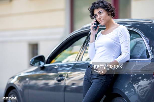 young woman leaning on her car, talking on her phone. - vanguardians stock pictures, royalty-free photos & images