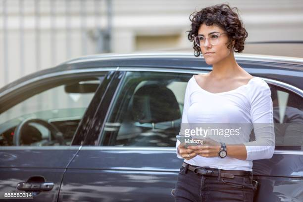 Young woman leaning on her car, using her smartphone.