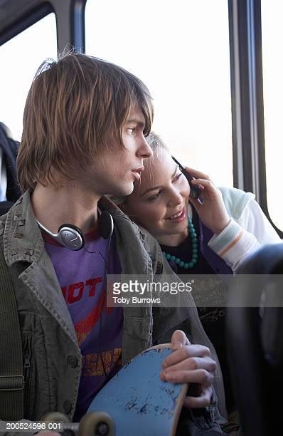 Young woman leaning on man using mobile phone on bus