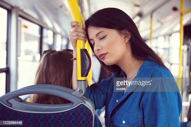 junge frau lehnt sich auf stange in bus - izusek stock-fotos und bilder