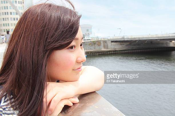 Young woman leaning on railings overlooking river