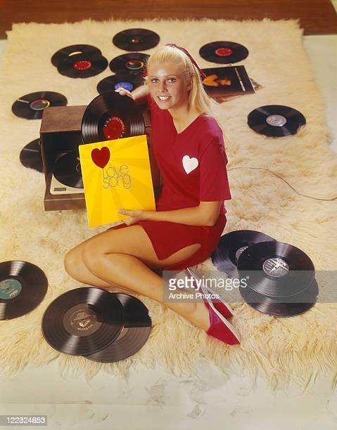 Young woman leaning on record player with record, smiling, portrait
