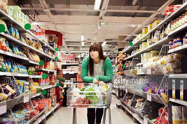 Young woman leaning on shopping cart at supermarket aisle