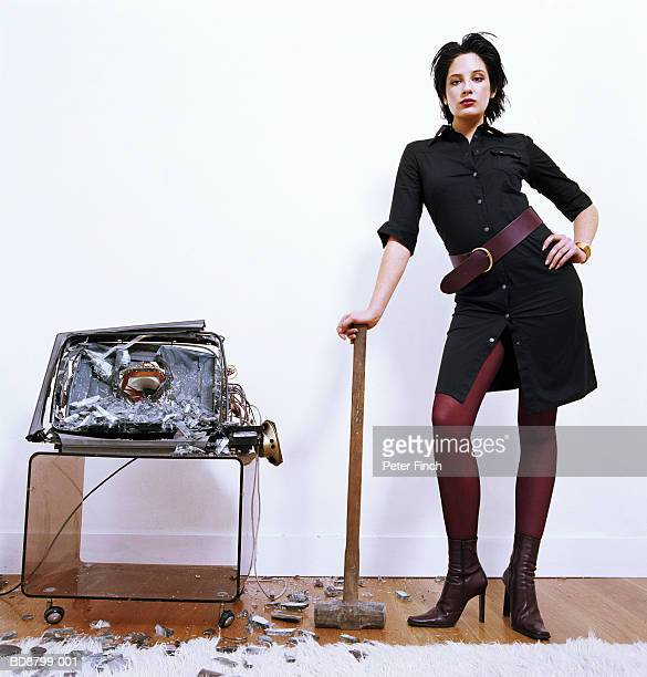 Young woman leaning on sledgehammer beside smashed television