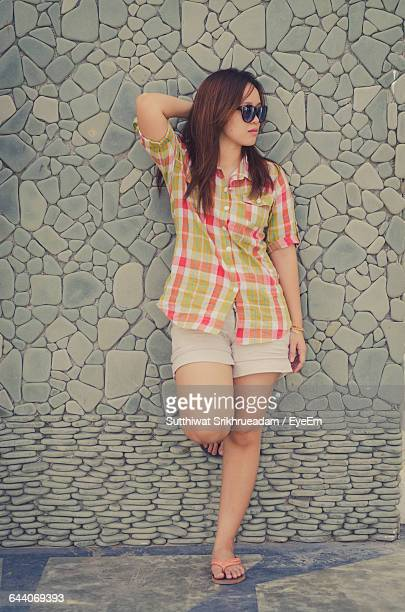 Young Woman Leaning On Stone Wall
