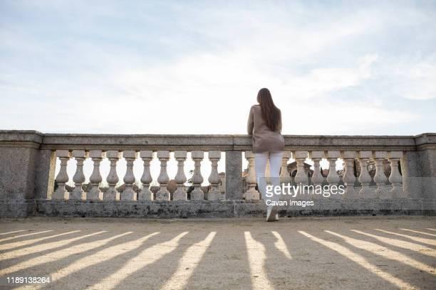 young woman leaning on the railing in boadilla del monte - palácio imagens e fotografias de stock