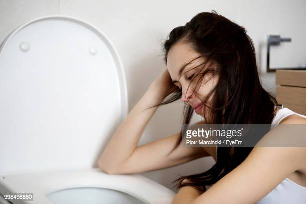young woman leaning on toilet bowl - hangover stock photos and pictures