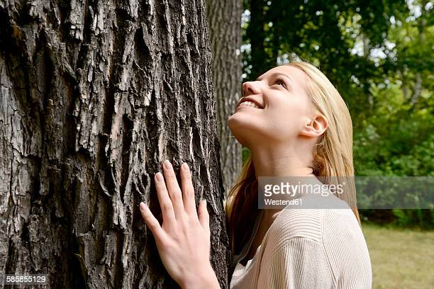 Young woman leaning on tree trunk