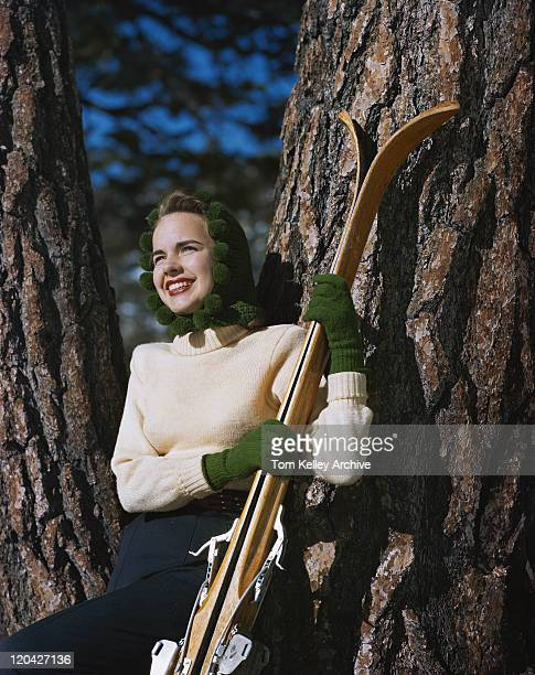 young woman leaning on tree with skis, smiling  - 1948 stock pictures, royalty-free photos & images