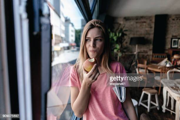 young woman leaning on window, eating apple - apple fruit stock photos and pictures