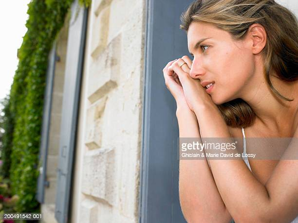 young woman leaning on window sill, close-up, side view - saint ferme stock photos and pictures