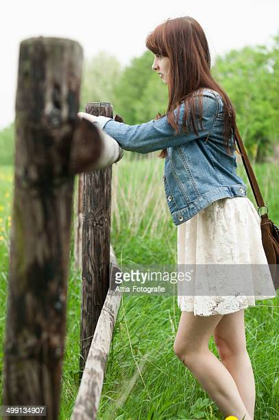 Young woman leaning on wooden fence