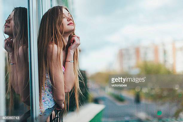 Young woman leaning out of a window in city, Seville, Spain