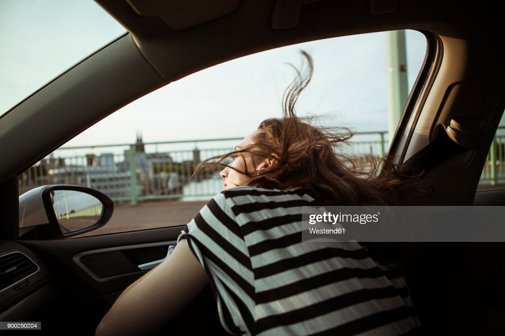 Young woman leaning out of car window : Stock Photo
