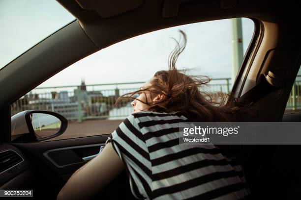 young woman leaning out of car window - unterwegs stock-fotos und bilder