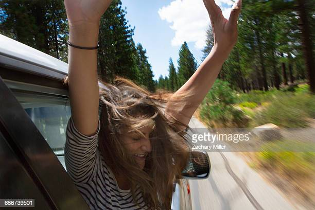 'Young woman leaning out of moving car window, Mammoth Lakes, California, USA'