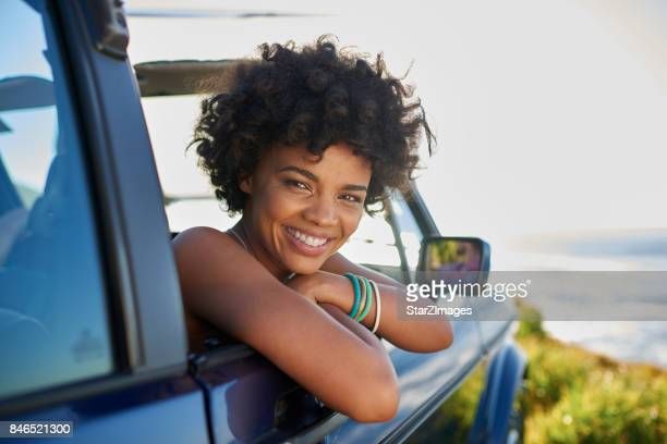 Young woman leaning out the window of car