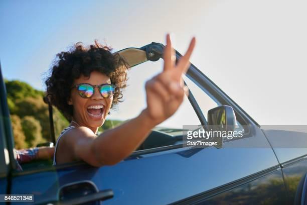Jonge vrouw leunend uit het raam van de auto