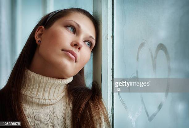 Young Woman Leans Against Window with Hearts Drawn in Frost