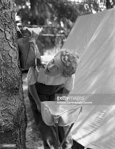 A young woman leans over to drink from a hanging flask at a campsite Padova Italy 1950