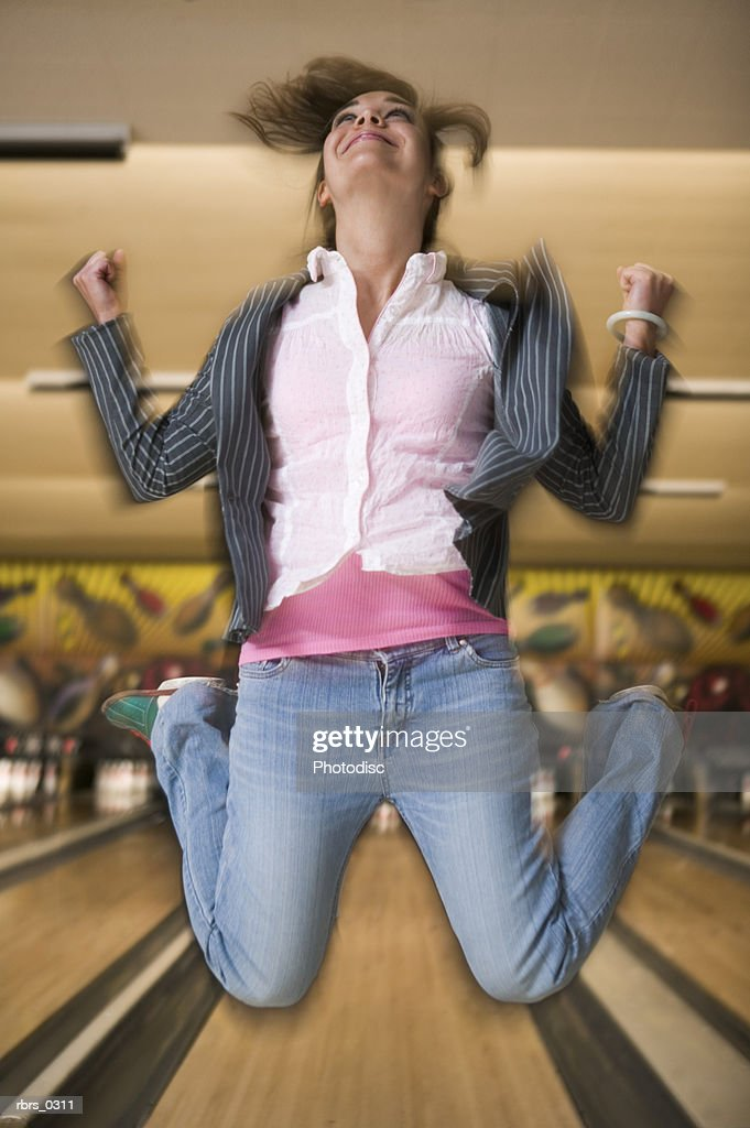 Young woman leaping in a bowling alley : Foto de stock