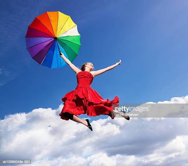 Young woman leaping in air, holding umbrella, smiling