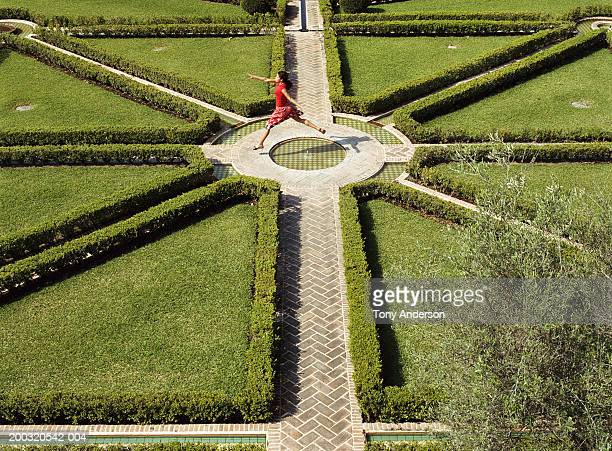 Young woman leaping in garden, elevated view