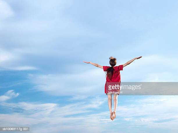 young woman leaping in sky, arms outstretched, rear view - 空中 ストックフォトと画像