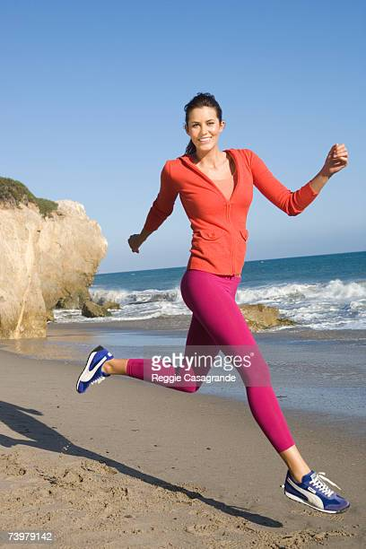 young woman leaping on beach, smiling, portrait - sportswear stock pictures, royalty-free photos & images