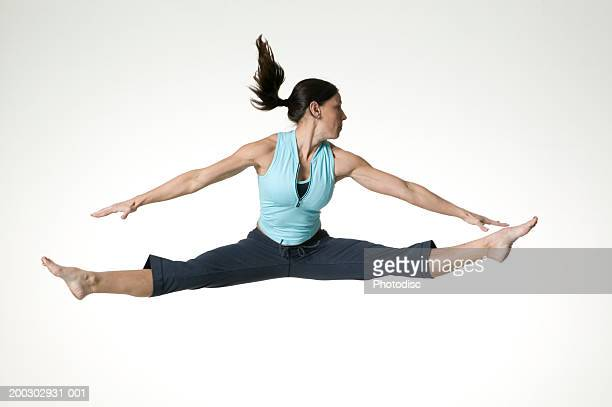 Young woman leaping with arms and legs outstretched, posing in studio, portrait