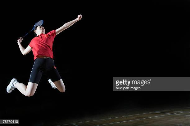 Young woman leaps high in the air and prepares to smash a shuttlecock during a game of badminton.