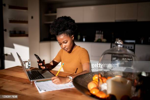 young woman learning online with laptop and phone, she is taking notes in a notebook - concentration stock pictures, royalty-free photos & images