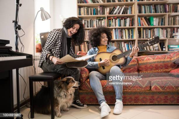 Young woman learning playing guitar with Music Teacher