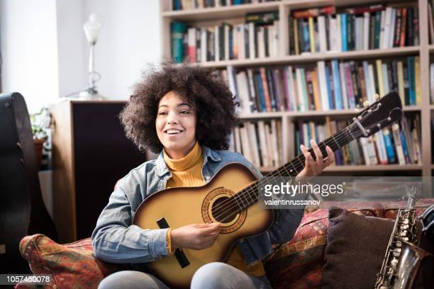 young woman learning playing guitar with music teacher - acoustic guitar stock pictures, royalty-free photos & images