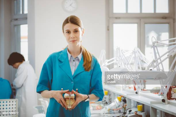 young woman learning prosthetic dentistry - izusek stock pictures, royalty-free photos & images