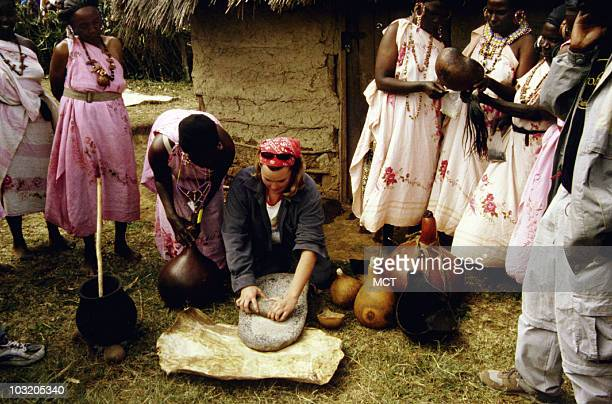 A young woman learns cooking skills from Kikuyu women in a village in Kenya
