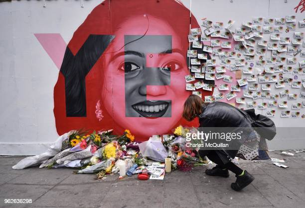 A young woman leaves flowers at the Savita Halappanavar mural as the results in the Irish referendum on the 8th amendment concerning the country's...