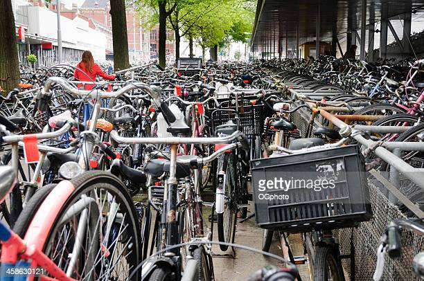 young woman leaving her bicycle at a parking garage - ogphoto stock photos and pictures