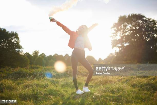 Young woman letting off smoke flare in sunlit field