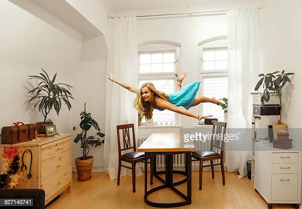 Young woman levitating in study